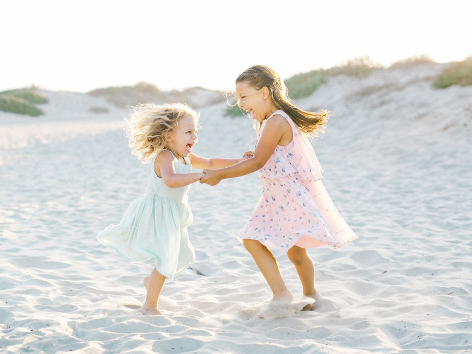 Sisters playing in the sand at Hotel Del Coronado Family Beach Photos | | light and airy Coronado family session shot on film by Mandy Ford