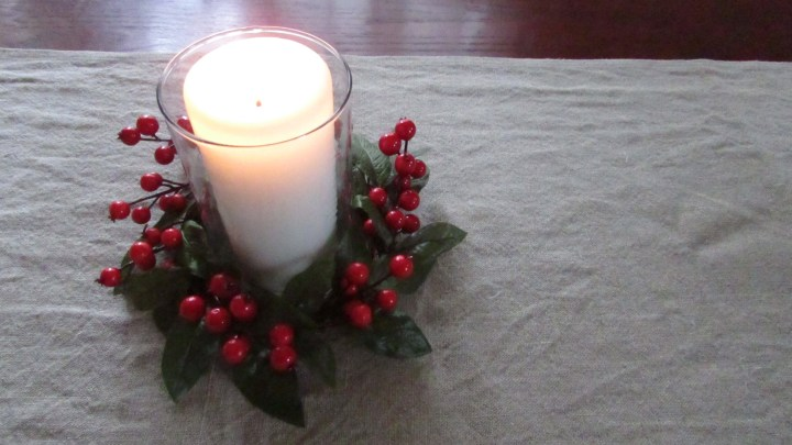 Red and green candle ring with lit candle