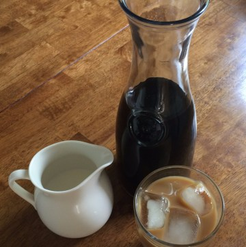 carafe of cold brew, creamer, with glass of iced coffee