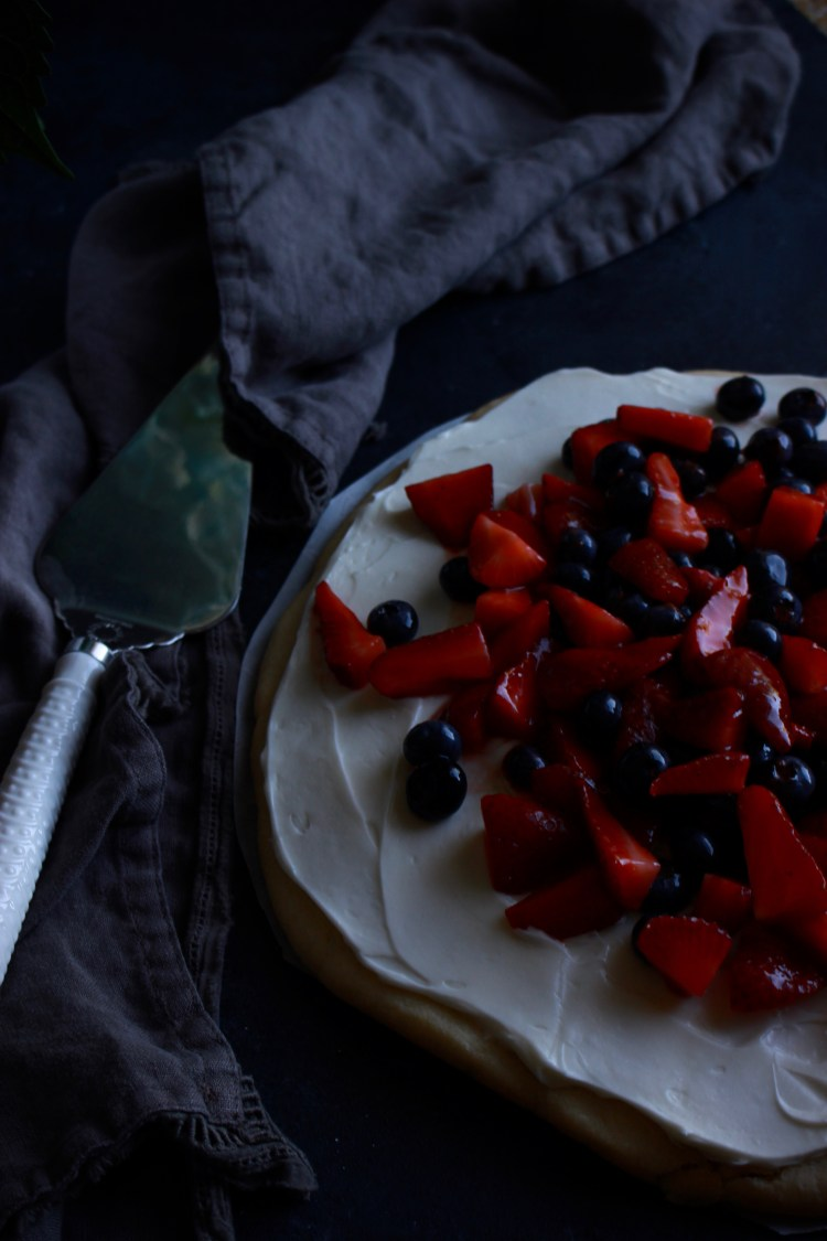 An easy red white and blue fruit pizza with homemade sugar cookie crust, cream cheese frosting, that's topped with glazed strawberries and blueberries. A crowd-pleasing patriotic dessert that's perfect for 4th of July cookouts!