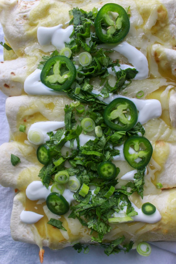 baked chicken enchiladas topped with sour cream, jalapeno, and cilantro