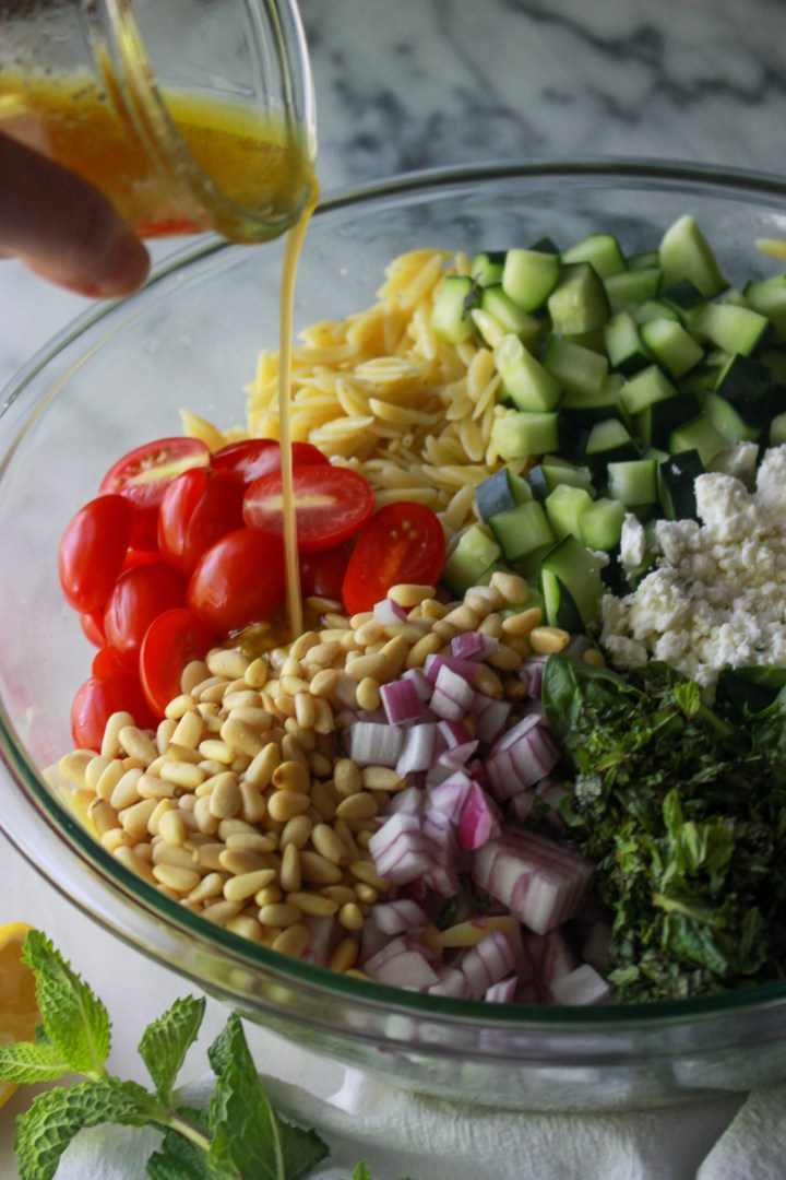 pouring dressing onto orzo salad