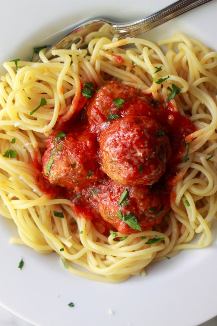 homemade italian slow cooker meatballs on spaghetti