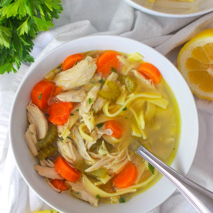 bowl of chicken noodle soup with lemon and parsley