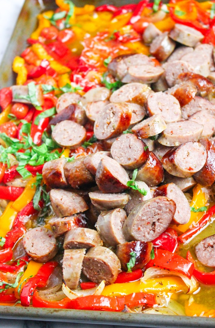 sliced sausage on sheet pan with peppers and onions