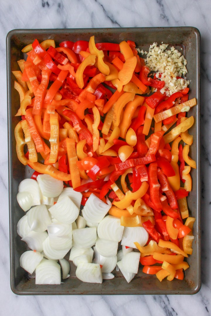 sliced bell peppers, onions, and minced garlic on sheet pan