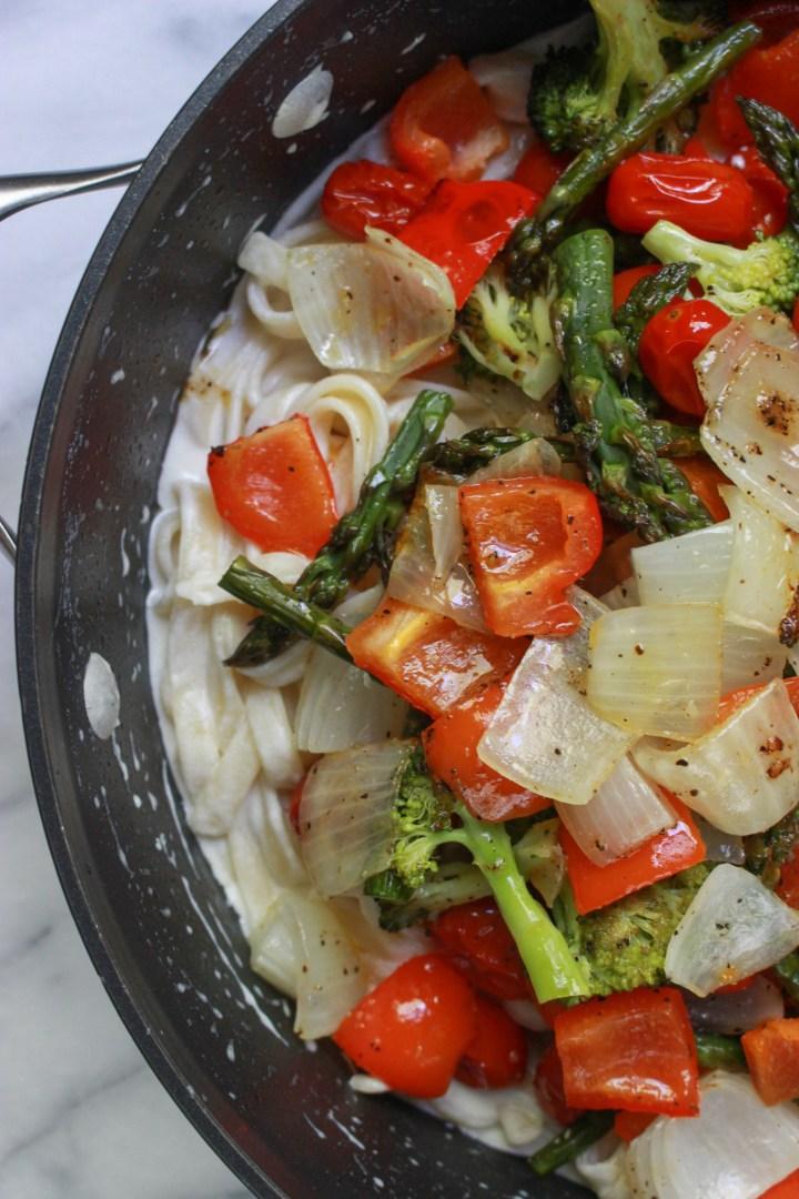 stirring roasted veggies into creamy fettuccini