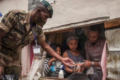 Madagascar soldiers distribute masks and herbal tea to people in the capital of Antananarivo on April 22, 2020.PHOTO: AFP