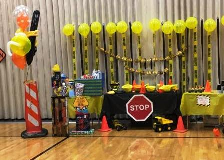 Construction party table with balloons and caution tape and construction printable banner from a FREE Construction Party Printables via Mandy's Party Printables