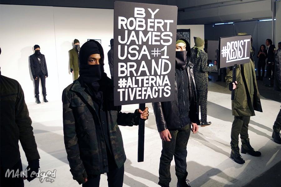 A shot showcasing various models holding political signage at men's fashion week.