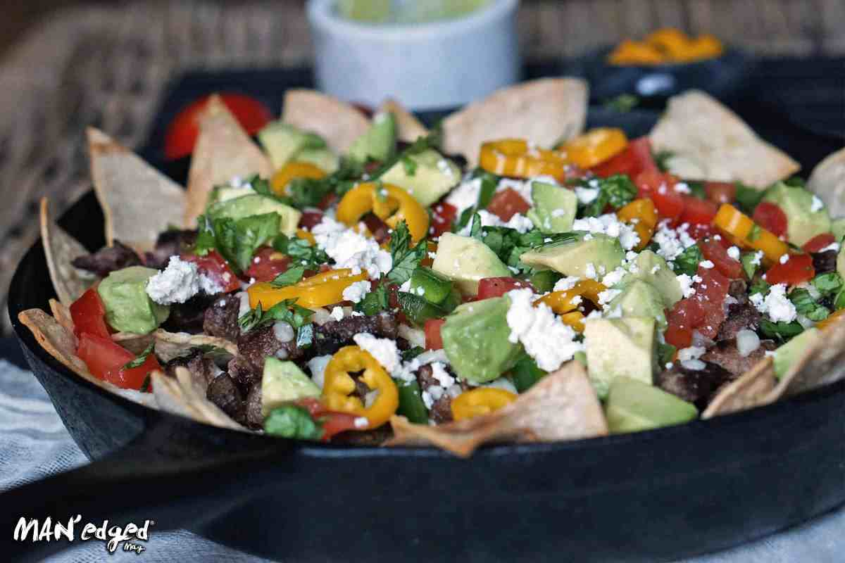 nacho plate filled with cheese, avocado, and meat