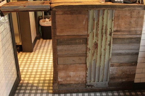 Bar counter egress. Salvaged column and woods, wrought iron with historic remnants