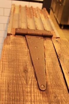 Bar counter egress. Salvaged column and woods, wrought iron.
