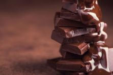 stock-photo-melted-chocolate-pouring-into-a-piece-of-chocolate-bars-with-green-mint-leaf-on-a-table-1012921762.jpg