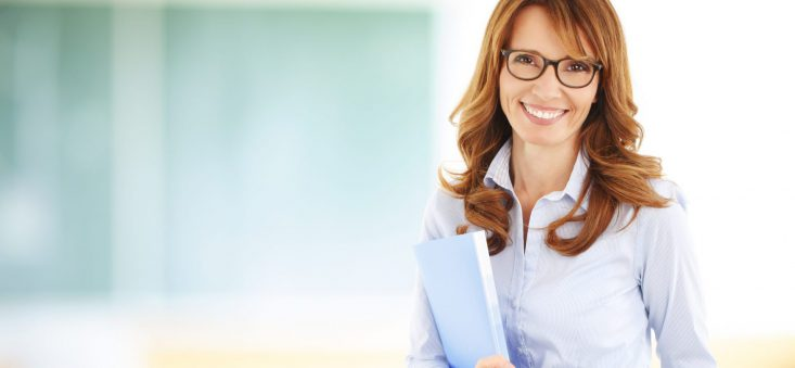 Middle age teacher standing in front of blackboard at classroom.