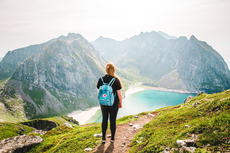 Girl with backpack enjoying the view while hiking Ryten in Lofoten, Norway