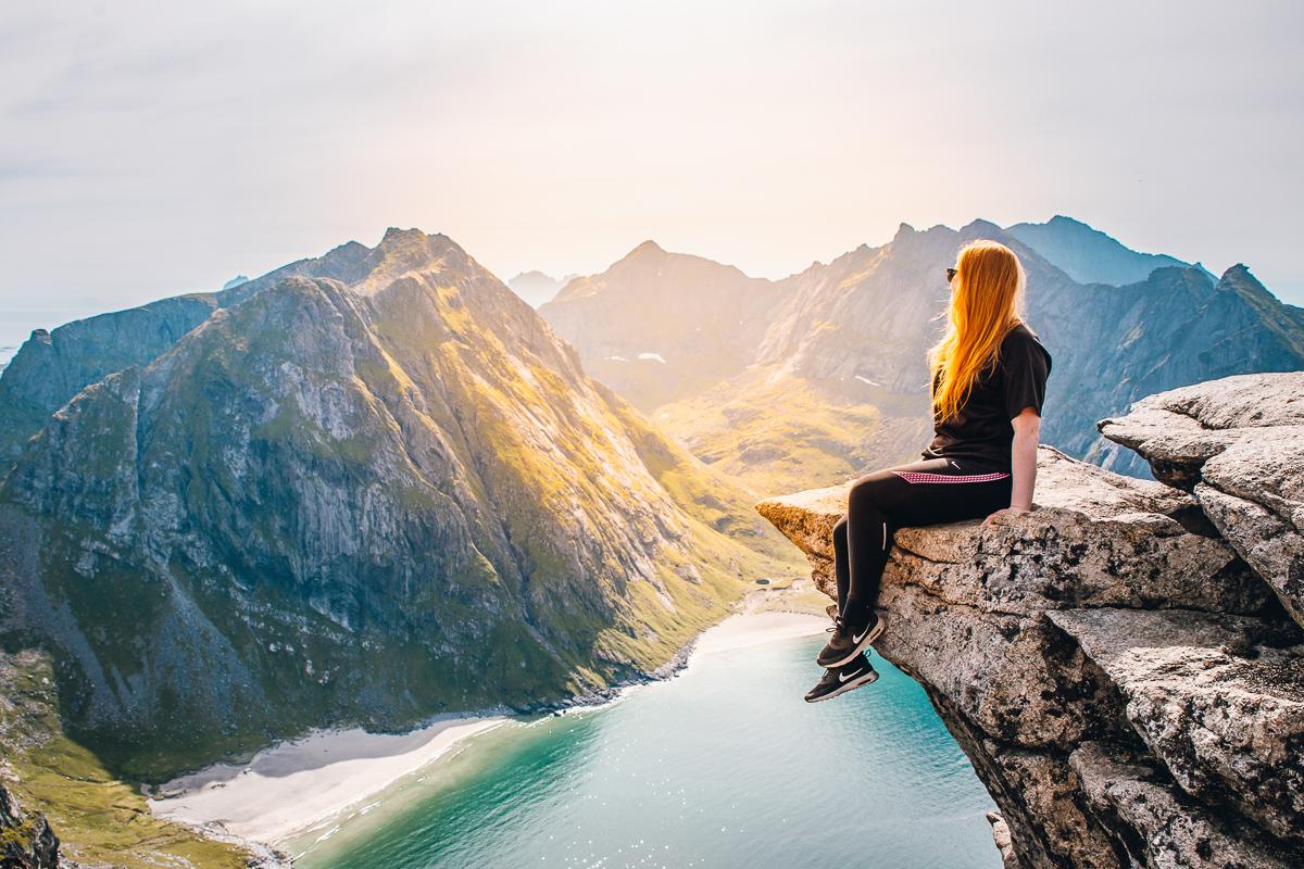 Girl enjoying the view of Kvalvika Beach from the Ryten summit in Lofoten, Norway