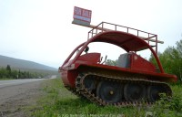 An old red snowmobile sits for sale on the side of a two-lane highway in southwest Newfoundland..