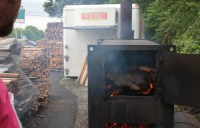The coalmaster watches as wood burns down to coals.