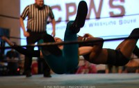 Two wrestlers fall to the mat, amrs locked, while the referee watches