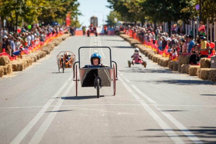 Boy racing billy cart down main street Australian Billy Cart Championships at corowa