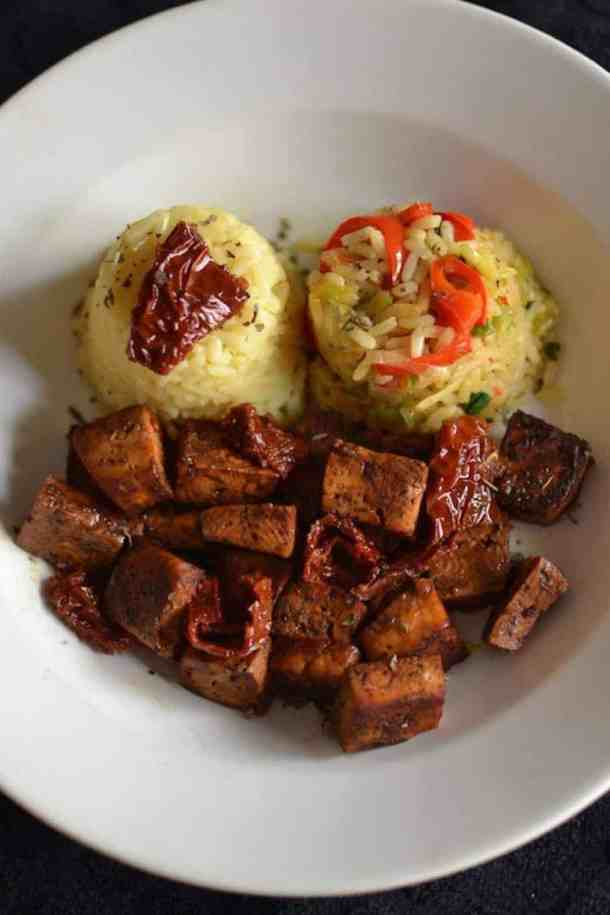Close-up View of Baked Tofu with Two Scoops of Vegetable Rice in a White Dish