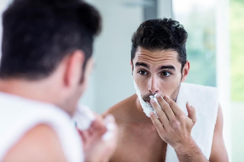 Guy Shaving In A Shower