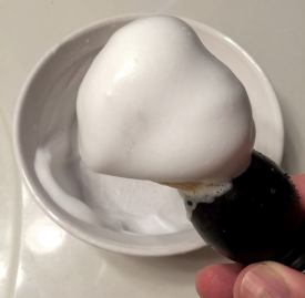 Building lather with shaving cream and boar shaving brush in shaving bowl