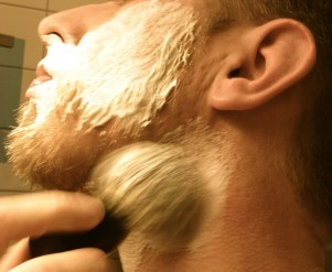 Style a beard with a razor after applying shaving cream with brush