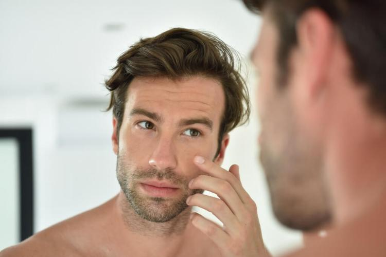 Applying face moisturizer for men