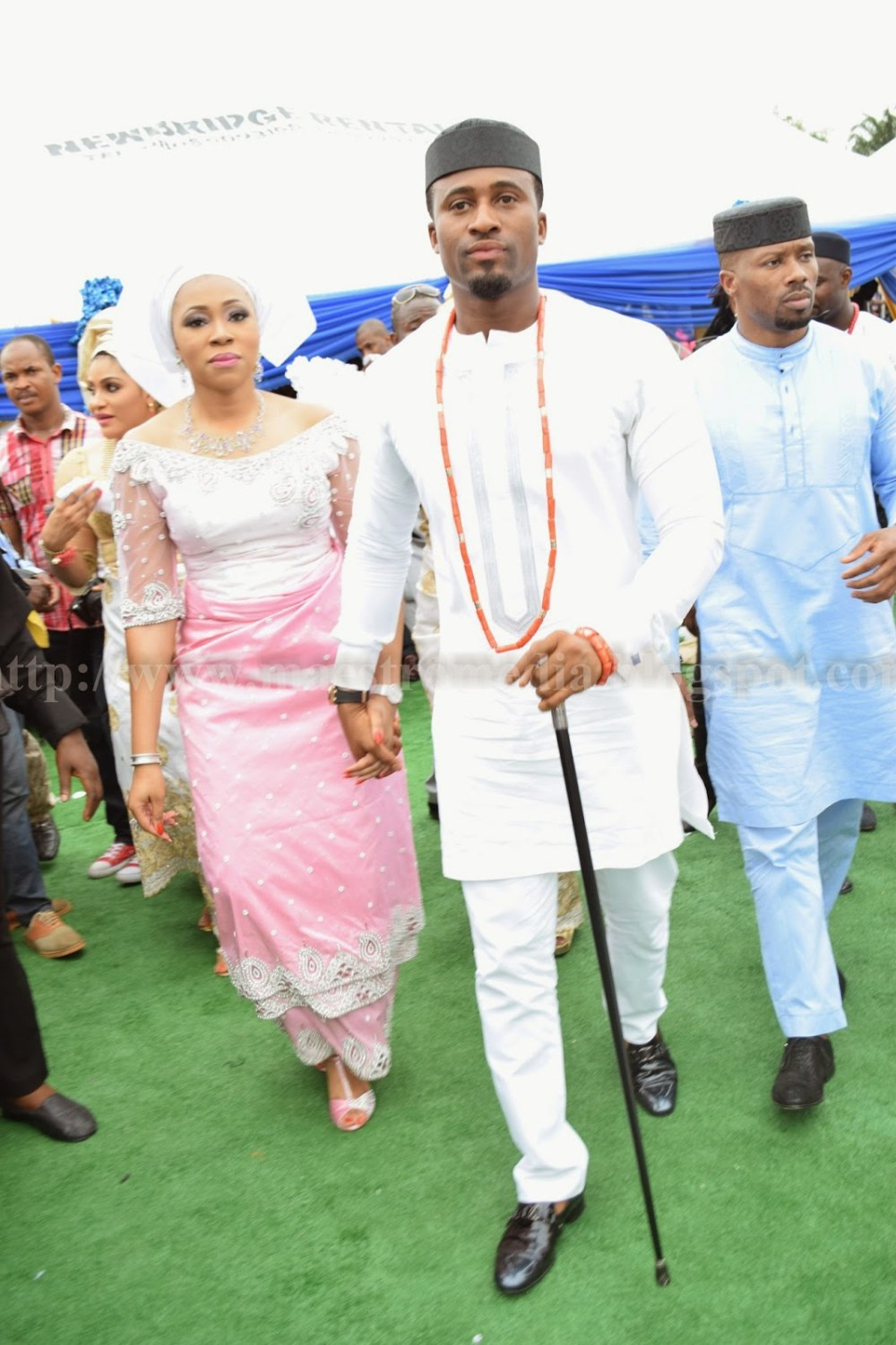 White traditional outfit, the black cap and red bead makes it look like an igbo attire