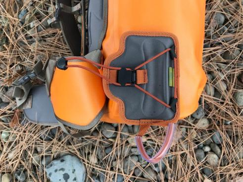 This photo shows the Fishpond Quickshot Rod Holder attached to a backpack.