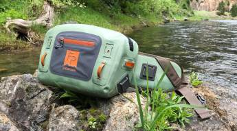 This photo shows the Fishpond Thunderhead Submersible Lumbar Pack on a rock outside.