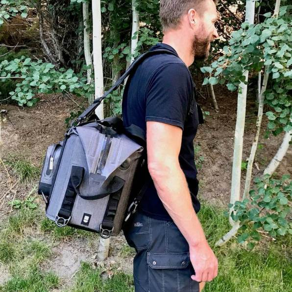 This photo shows a man carrying the ICEMULE Traveler cooler in backpack mode from a side view.