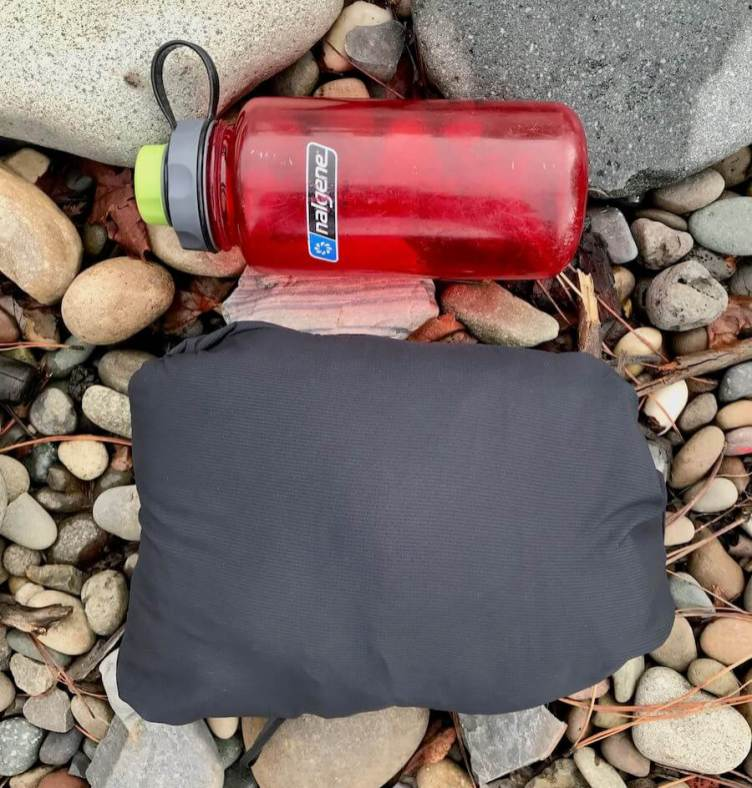 This photo shows the Black Diamond First Light Stretch Hoody packed into its pocket next to a water bottle as a size reference.