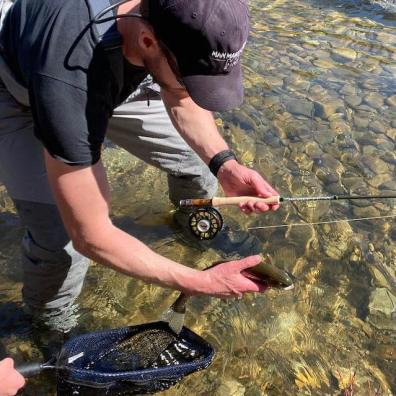 This photo shows a fly fisherman releasing a trout while wearing the Korkers Terror Ridge Wading Boots.