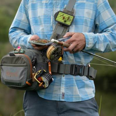 This fly fishing hip pack photo shows the Fishpond Switchback Pro Wading Belt System with the pack rotated to the front while being worn by an angler.