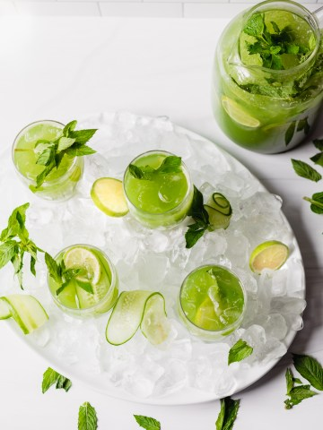 a pitcher filled to the top with cucumber ginger mint agua fresca along with four small glasses filled to the top and garnished with sliced limes, mint leaves, and cucumber slices. The glasses are on an oval platter filled with ice while the pitcher is on a flat surface in the upper right hand corner