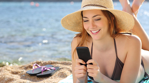 Mädchen am Strand flirtet per SMS