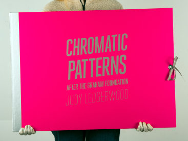 """Deluxe edition portfolio: """"Chromatic Patterns After the Graham Foundation"""", 2014. Three lithographs with relief and aluminum dust by Judy Ledgerwood and a poem by John Yau, housed in custom portfolio case. Yau's poem, """"26 Letters for Judy Ledgerwood"""", is silkscreened in silver ink. Poem and prints are 22″ x 30″. The portfolio case is covered in pink fabric with title and colophon silkscreened in silver. Grommet and grosgrain ribbon closure. The deluxe edition is limited to 8 sets."""