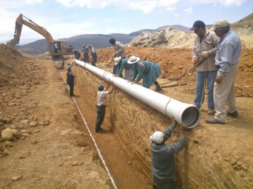 Mano a Mano staff and community volunteers installing tubing at the Wirkini water reservoir project site.