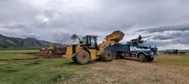 Loader loading material onto dump truck for Toro Toro airstrip construction, April 2021.