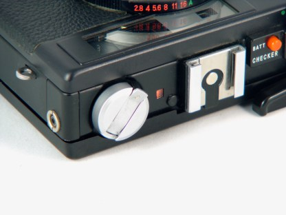 The red/green indicator next to the rewind knob tells if there is a film inside the camera. The small black rounded cover hdies the rangefinder adjustment screw.