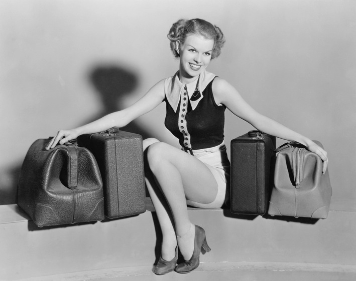 Vintage black and white woman with suitcases on bench