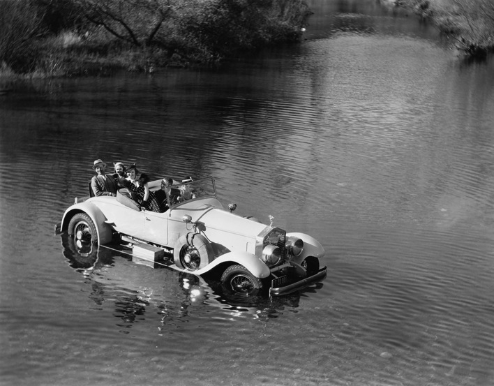 Happy people on road trip car stuck in river black and white vintage