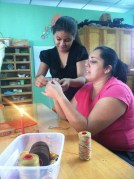 A girl in a black shirt, standing, works with a woman in a pink shirt, seated at a table, to make jewelry.
