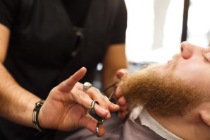 Professional hairdresser wearing black gloves cutting beard of client with scissors at barbershop. Bearded man getting beard haircut at barber salon