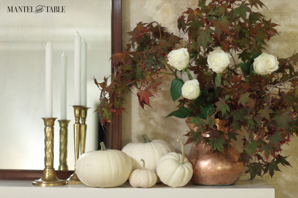 White pumpkins on the mantel. Copper pitcher with fall leaves & white roses on the right, brass candle sticks & white candles on the left in front of a dark wood mirror.