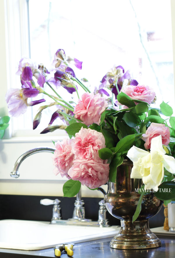 Pink roses, yellow roses, purple iris in a silver wine bucket on the counter by the sink