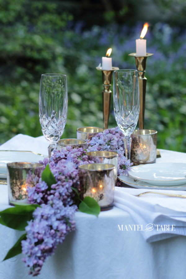 formal outdoor dinner table for two with candles, white tablecloth, lilacs.